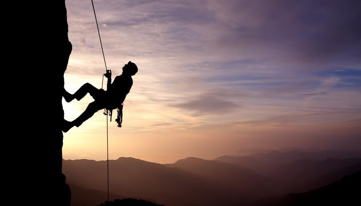 rock climber on steep cliff with harness