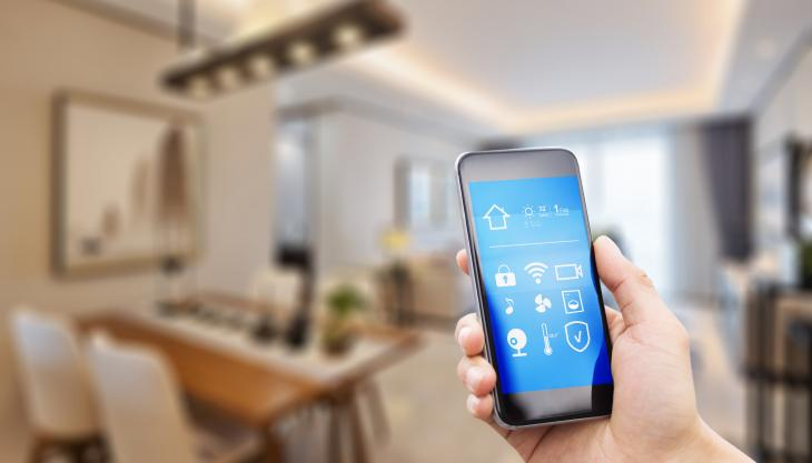 Image of a mobile phone in a home that is able to control the indoor temperature, security and entertainment systems