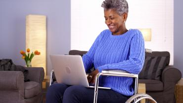 Elderly black woman talking to someone on her laptop