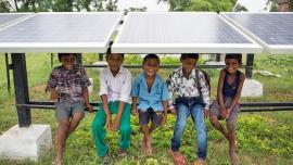 Smiling children sitting underneath a solar PV panel