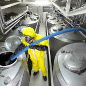 Chemical plant worker filling tank in factory
