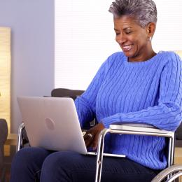 Elderly black woman talking to someone on her laptop