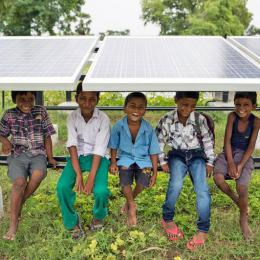 Smiling children sitting underneath a solar PV panel