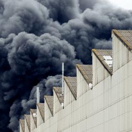 Black plumes of smoke from an accidental toxic industrial fire as seen from a behind a factory building