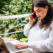 Woman working on phone and computer