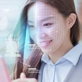 Woman using smartphone with facial recognition